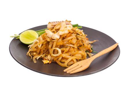 cebollines: Pat Thai, fideos de arroz frito con queso de soja, verduras, huevo en un plato negro.