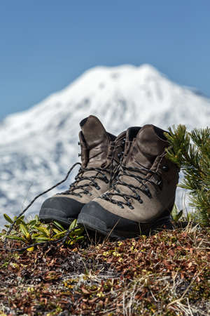 the far east: Old tourist boots on background volcano on Kamchatka Peninsula. Far East, Russia.
