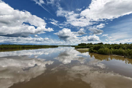 kamchatka: Beautiful summer landscape: view on Kamchatka River beautiful clouds and reflection in water. Russia Far East Kamchatka Peninsula. Stock Photo