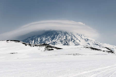 wintry weather: Wintry mountain landscape of Kamchatka Peninsula: view of active Koryak Volcano Koryakskaya Sopka and beautiful clouds in cloudy weather. Kamchatka Far East Russia. Stock Photo