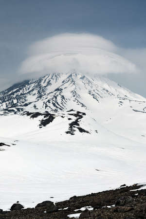 Wintry mountain landscape of Kamchatka: beautiful view of Koriaksky Volcano Koryakskaya Sopka and clouds enveloping the top of the active volcano. Kamchatka Far East Russia.