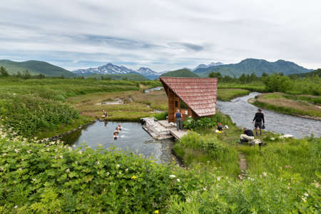 far east: NALYCHEVO, KAMCHATKA PENINSULA, RUSSIA - JULY 11, 2014: Goryacherechensky group hot springs in nature park Nalychevo, tourists swimming in the natural thermal pools. Russia, Far East, Kamchatka. Editorial