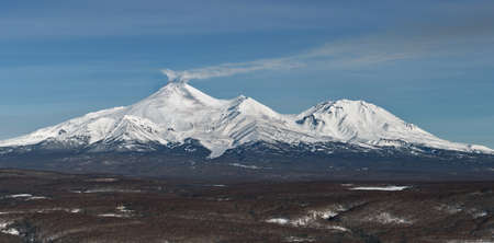 effusion: Panorama view of the volcanoes of Kamchatka: Avachinsky Volcano and Kozelsky Volcano on a sunny day. Russia, Far East, Kamchatka Peninsula.