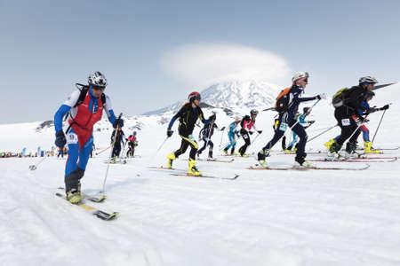 KORYAK, AVACHA VOLCANOES, KAMCHATKA, RUSSIA - APRIL 27, 2014: Mass start race, ski mountaineers climb on skis on mountain. Team Race ski mountaineering Asian, ISMF, Russian, Kamchatka Championship.
