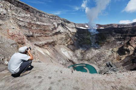 fumarole: KAMCHATKA, Rusia - 21 de julio 2013: Turismo en el cr�ter activo del volc�n Gorely rodaje del volc�n actuando fumarola y el lago del cr�ter. Rusia, Lejano Oriente, la pen�nsula de Kamchatka.