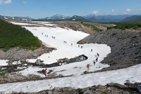 traverse: KAMCHATKA, RUSSIA - JULY 10, 2014: Tourists traverse mountain river walking on snowfield in summer sunny day. Russia, Far East, Kamchatka Peninsula.