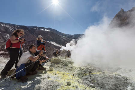fumarole: KAMCHATKA, RUSSIA - SEPTEMBER 11, 2013: Crater active Mutnovsky Volcano on Kamchatka: group tourists near the sulfur fumarole in the cloud of steam and gas. Kamchatka Peninsula, Russia, Far East.