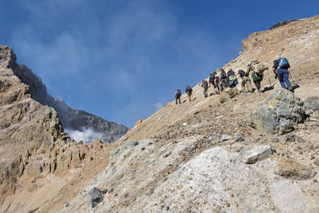 volcano slope: KAMCHATKA, RUSSIA - SEPTEMBER 11, 2013: Group of tourists climbing on the steep slope to the active crater Mutnovsky Volcano. Kamchatka Peninsula, Russia, Far East. Editorial