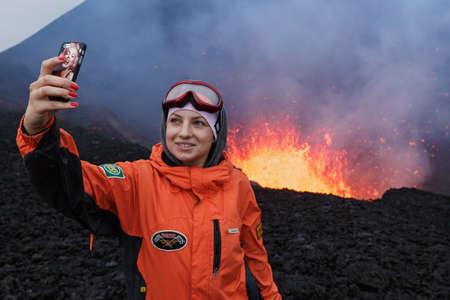 peligro: KAMCHATKA, Rusia - 27 de julio 2013: Erupción del volcán Tolbachik en Kamchatka, chica fotografiada selfie en el lago de fondo de lava en el cráter del volcán. Rusia, Lejano Oriente, la península de Kamchatka.