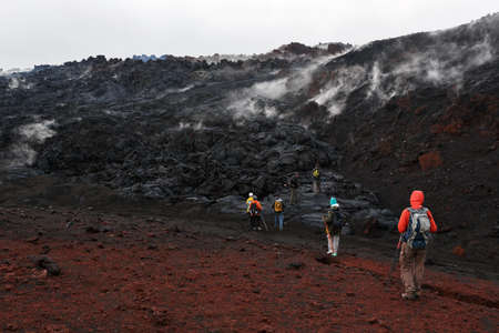 kamchatka: KAMCHATKA, RUSSIA - JULY 27, 2013: Group of tourists hiking on the lava field eruption Tolbachik Volcano on Kamchatka. Russia, Far East, Kamchatka Peninsula. Editorial