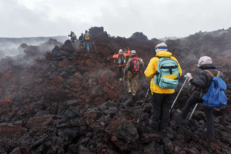 eruptive: KAMCHATKA, RUSSIA - JULY 27, 2013: Group of tourists hiking on the lava field eruption Tolbachik Volcano on Kamchatka Peninsula. Russia, Far East. Editorial