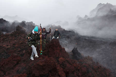 eruptive: KAMCHATKA, RUSSIA - JULY 27, 2013: Group of tourists hiking on the lava field eruption active Tolbachik Volcano on Kamchatka Peninsula. Russia, Far East. Editorial