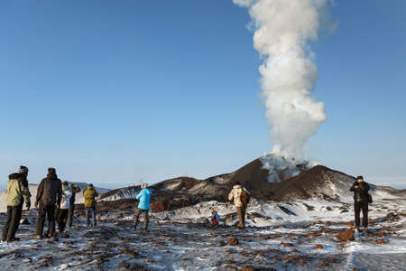 eruptive: TOLBACHIK VOLCANO, KAMCHATKA, RUSSIA - FEBRUARY 2, 2013: Tourists watching the eruption of active Tolbachik Volcano, ejecting lava, ash, steam and gas. Russia, Far East, Kamchatka Peninsula.