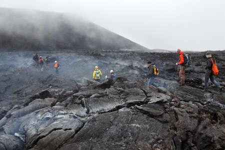 lava field: KAMCHATKA, RUSSIA - JULY 27, 2013: Tourists hiking on hot and steaming lava field eruption Tolbachik Volcano on Kamchatka Peninsula. Russia, Far East. Editorial