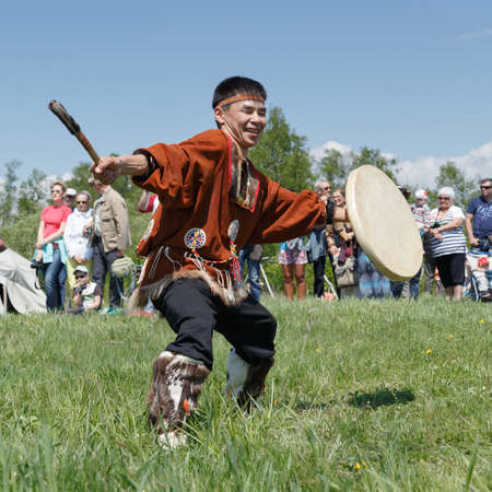 aborigine: ELIZOVO, KAMCHATKA, RUSSIA - JUNE 15, 2013: Man in clothes indigenous people of Kamchatka dancing with a tambourine. Celebration of Day of the first fish - ritual celebration aborigine of Kamchatka.