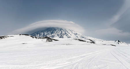 wintry weather: Wintry panoramic mountain landscape of Kamchatka: view of active Koryaksky Volcano and beautiful clouds in cloudy weather. Kamchatka Peninsula Far East Russia.