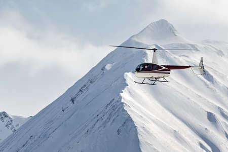 lejano oriente: KAMCHATKA, Rusia - 09 de marzo 2013: Helicóptero Robinson R44 Astra volando sobre las montañas en el Kamchatka en el hermoso clima nublado. Rusia, Lejano Oriente, la península de Kamchatka.