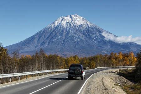 lejano oriente: KAMCHATKA, Rusia - 30 de septiembre 2012: Opinión del otoño del coche va en el camino al Volcán Koryaksky activa en la península de Kamchatka en un día sin nubes soleado con cielos azules. Rusia, Lejano Oriente.