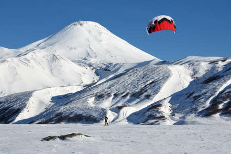 snowkiting: KAMCHATKA, AVACHA VOLCANO, RUSSIA - NOVEMBER 22, 2014: Snowkiting or kiteboarding - sportsman glides on skis on snow on a background of active Avachinsky Volcano Avacha Volcano on sunny day.
