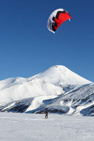 snowkiting: KAMCHATKA, AVACHA VOLCANO, RUSSIA - NOVEMBER 22, 2014: Kiteboarding or Snowkiting - sportsman glides on skis on snow on a background of active Avacha Volcano Avachinsky Volcano on sunny day.