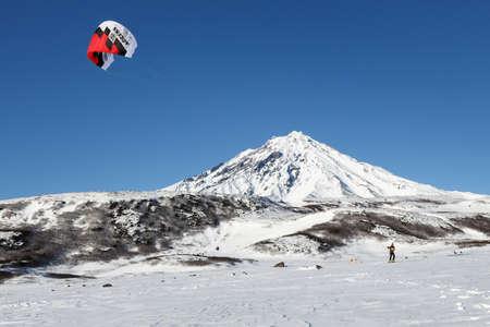 kiteboarding: KAMCHATKA, KORIAKSKY VOLCANO, RUSSIA - NOVEMBER 22, 2014: Snowkiting or kiteboarding - sportsman glides on skis on snow on a background of active Koriaksky Volcano Koryaksky Volcano on sunny day.