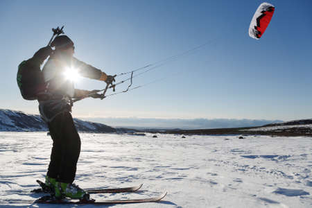 snowkiting: KAMCHATKA PENINSULA, RUSSIA - NOVEMBER 22, 2014: Snowkiting or kiteboarding - sportsman glides on skis on snow in sunny weather at sunset. Editorial