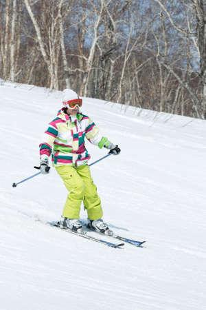 far east: MOROZNAYA MONTA�A, Yelizovo, KAMCHATKA, Rusia - 17 de abril de 2015: esquiador de la mujer joven en traje de colores bajando la pendiente en un d�a soleado. Pen�nsula de Kamchatka, Extremo Oriente, Federaci�n de Rusia. Editorial