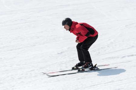 lejano oriente: MOROZNAYA MONTA�A, Yelizovo, KAMCHATKA, Rusia - ABR 17 de, 2015: esquiador en el equipo rojo y negro que bajaba la pendiente y sin bastones de esqu� en un d�a soleado. Pen�nsula de Kamchatka, Extremo Oriente, Federaci�n de Rusia.