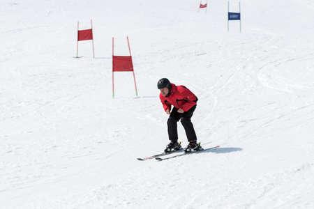 lejano oriente: MOROZNAYA MONTAÑA, Yelizovo, KAMCHATKA, Rusia - ABR 17 de, 2015: esquiador en el equipo rojo y negro que bajaba la pendiente y sin bastones de esquí en un día soleado. Federación de Rusia, Lejano Oriente. Península de Kamchatka.