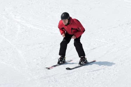 lejano oriente: MOROZNAYA MONTAÑA, Yelizovo, KAMCHATKA, Rusia - ABR 17 de, 2015: esquiador en el equipo rojo y negro que bajaba la pendiente y sin bastones de esquí en un día soleado. Lejano Oriente ruso. Península de Kamchatka.