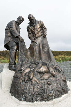 fishermans net: UST-KAMCHATSKY, KAMCHATKA, RUSSIA - SEP 20, 2015: View of Monument to fishermen, or Monument to Fishermans glory two fishermen pulling a fishing net with fish. Kamchatka Peninsula, Far East Russia.