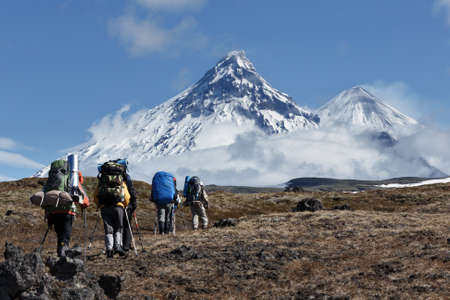 lejano oriente: Hiking on the Kamchatka Peninsula: travelers go to the mountains in the background volcanoes: Kamen Volcano, active Klyuchevskoi Volcano and active Bezymianny Volcano on a sunny day. Russia, Far East, Kamchatka.