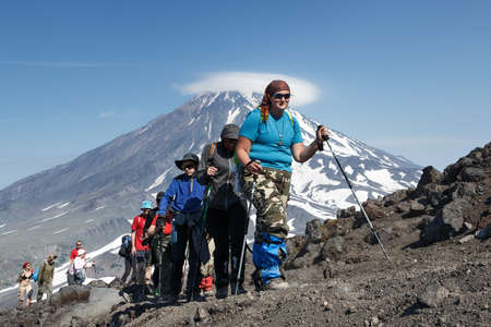 lejano oriente: AVACHA VOLCANO, KAMCHATKA, RUSSIA - JULY 08, 2014: Hiking on the Kamchatka Peninsula - a group of tourists go hiking and climbing to the top of Avacha Volcano on background of Koryak Volcano. Russia, Far East. Editorial