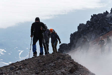 active volcano: AVACHA VOLCANO, KAMCHATKA, RUSSIA - JULY 08, 2014: Hiking on Kamchatka - a group of tourists climbing to the top crater of active Avachinsky Volcano on Kamchatka Peninsula Russian Far East. Editorial