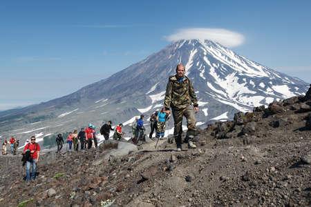 far east: AVACHA VOLCANO, KAMCHATKA, RUSSIA - JULY 08, 2014: Hiking on the Kamchatka Peninsula - a group of tourists climbing to the top of Avacha Volcano on a background of Koryak Volcano. Russian Far East, Kamchatka.