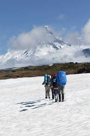 lejano oriente: Senderismo en la pen�nsula de Kamchatka: un grupo de turistas escalada campo de nieve en un fondo hermoso del grupo Klyuchevskaya de los volcanes en un d�a soleado. Rusia, Lejano Oriente, Kamchatka. Foto de archivo