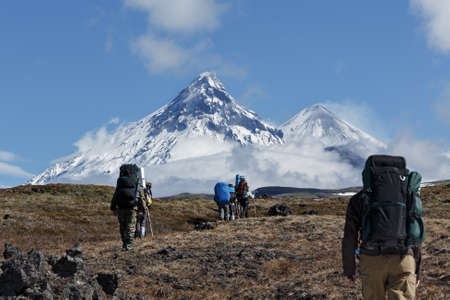 crater highlands: Hikers group trekking in the Kamchatka mountain on the background of Klyuchevskaya group of volcanoes: Kamen Volcano, active Klyuchevskoy Volcano and active Bezymianny Volcano on a sunny day. Russia, Far East, Kamchatka Peninsula. Stock Photo