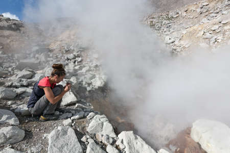 fumarole: DZENZUR VOLCANO, KAMCHATKA, RUSSIA - SEPTEMBER 04, 2014: Beautiful girl photographing the steaming smoking fumarole on the crater active Dzenzur Volcano on a sunny day. Eurasia, Russian Far East, Kamchatka Peninsula. Editorial