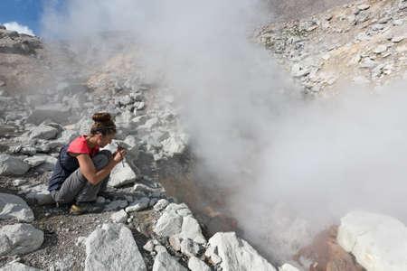 lejano oriente: VOLCÁN DZENZUR, KAMCHATKA, Rusia - 04 de septiembre de 2014: La muchacha hermosa fotografiar la fumarola fumar vapor en el volcán activo Dzenzur cráter en un día soleado. Eurasia, Lejano Oriente ruso, península de Kamchatka.