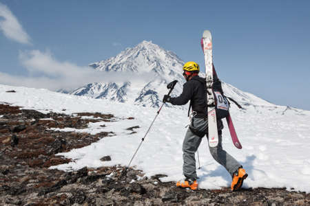 strapped: AVACHA VOLCANO, KAMCHATKA, RUSSIA - APR 21, 2012: Open Cup of Russia on ski-mountaineering on Kamchatka. Ski mountaineer climbing on mountain with skis strapped to backpack on background Koryak Volcano.