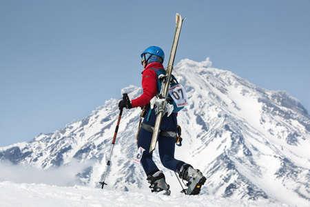 strapped: AVACHA VOLCANO, KAMCHATKA, RUSSIA - APR 21, 2012: Open Cup of Russia on ski-mountaineering. Girl ski mountaineer climbing on mountain with skis strapped to backpack on background active Koryak Volcano.