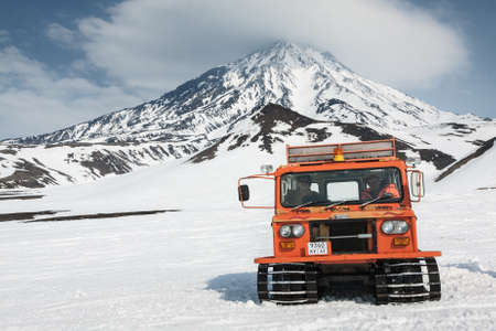 snowcat: AVACHA PASS, KAMCHATKA PENINSULA, RUSSIA - APR 22, 2012: Snowcat transportation for extreme sports sportsman skiers and snowboarders on the snowy slopes of the mountains. View snowcat with people on the background of the active Koryak Volcano.