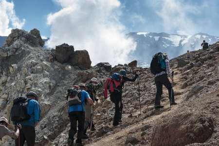 far east: Hiking group of people on a tourist track climb the steep slope to the crater of active Mutnovsky Volcano on sunny day. Eurasia, Far East, Russia, Kamchatka peninsula.