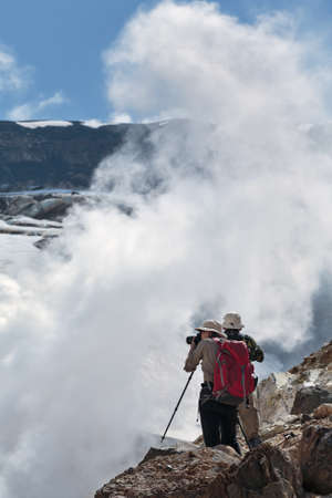 fumarole: Hiking in Kamchatka: two tourists photographing and looking the smoking steaming fumarole on crater active Mutnovsky Volcano on a sunny day. Eurasia, Far East, Russia, Kamchatka peninsula.