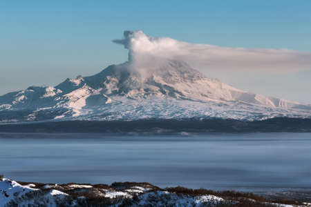 far east: Beautiful volcanic landscape of Kamchatka Peninsula: eruption active Shiveluch Volcano - emission from crater of volcano plume of gas, steam and ashes. View of volcano at sunrise. Eurasia, Far East, Russia, Kamchatsky Krai.