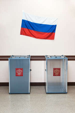 encuestando: Two ballot boxes for voting in the elections with coat of arms Russia and the national flag of the Russian Federation hanging on the wall in the polling station. Foto de archivo