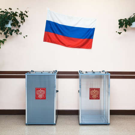 cast: Two ballot boxes for voting in the elections with coat of arms Russian Federation and the national flag of Russia the hanging on the wall in the polling station.