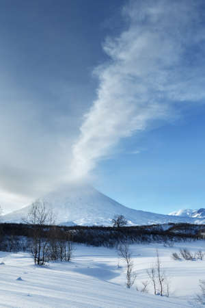 effusion: Beauty winterly landscape of Kamchatka: evening view of eruption active Klyuchevskoy Volcano Klyuchevskaya Sopka - eructation from crater of volcano plume of gas, steam and ashes. Eurasia, Far East, Russia, Kamchatsky Krai.