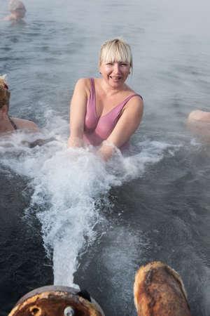 far east: Península de Kamchatka, Rusia - Feb 02, 2013: Mujer satisfecha relajarse en el spa geotérmica en la piscina de aguas termales en el invierno. Eurasia, Lejano Oriente de Rusia, Krai de Kamchatka, Anavgay Village.