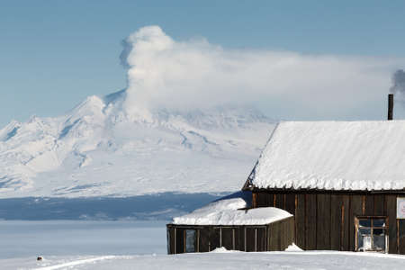 effusion: KAMCHATKA PENINSULA, RUSSIA - JANUARY 05, 2016: Winter view of the field wooden house Kamchatka volcanologists on the background eruption active Shiveluch Volcano. Eurasia, Russian Far East, Kamchatsky Krai.